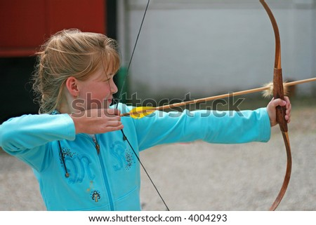Archer taking aim to hit the bull's eye - stock photo