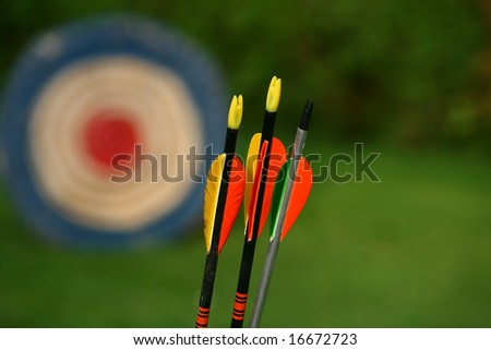 archery arrows and target on a green background - stock photo