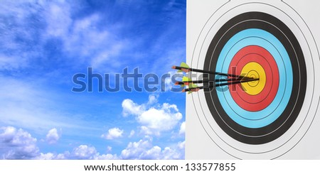 Archery target with arrow over blue sky background - stock photo