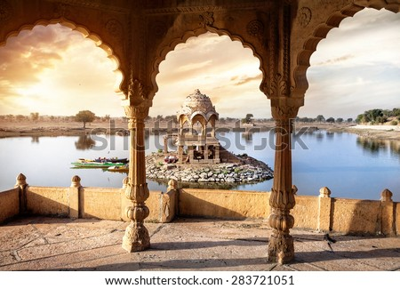 Arches and temple in Gadi Sagar lake at sunset sky in Jaisalmer, Rajasthan, India - stock photo