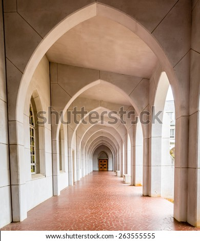 Arches into Distance toward wood door over tile walkway - stock photo