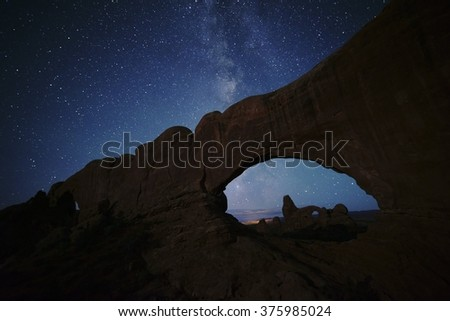 Arches National Park North Window, South Window, and Turret Arch under the Milky Way night sky in Autumn.   Stars are easy to see at night in the deserts of Utah near Moab.
