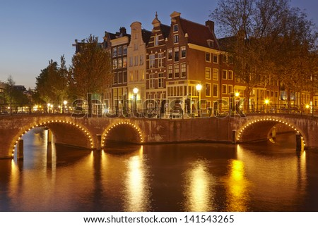 Arches of bridges and old houses at a canal in the evening (blue hour) in the capitol city of the Netherlands, Amsterdam.
