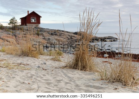 Archipelago in morning light. Rocks on the beach in the foreground, pines on a hill in the background - stock photo