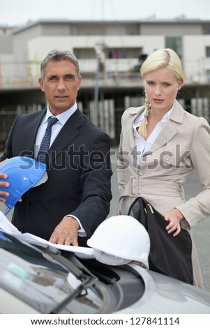 Architect and assistant arriving at construction site