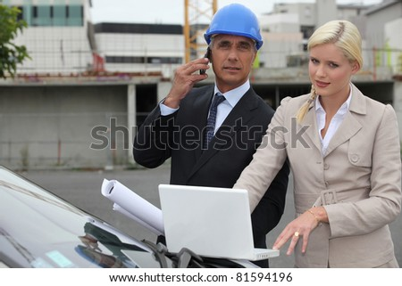 Architect and assistant stood by car with plan - stock photo