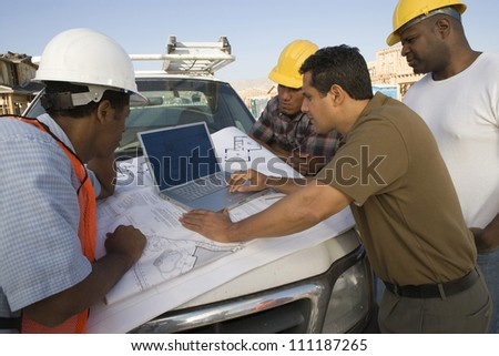Architect and builders discussing with laptop - stock photo
