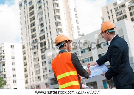 Architect and client discussing the plan of the building at the construction site, rear view - stock photo