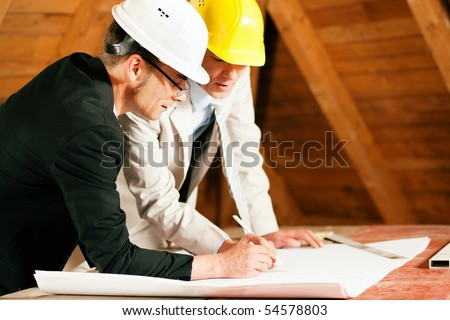 Architect and construction engineer or surveyor discussion plans and blueprints. Both are wearing hardhats and are standing on the construction site of a home indoors - stock photo