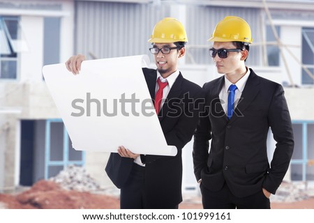 Architect and construction engineer or surveyor discussion plans and blueprints shot at construction site - stock photo