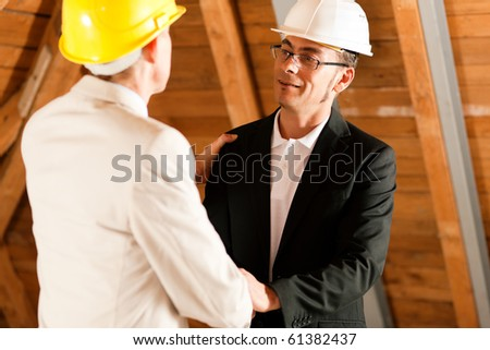 Architect and construction engineer or surveyor shaking hands, Both are wearing hardhats and are standing on the construction site of a home indoors - stock photo