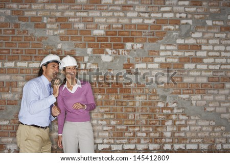 Architect and construction manager conversing against brick wall at site - stock photo
