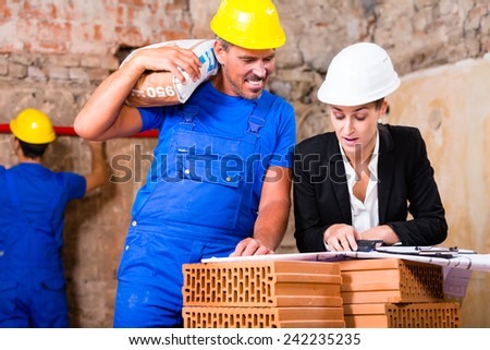 Architect and construction worker having sack of cement on shoulder on site with plan - stock photo
