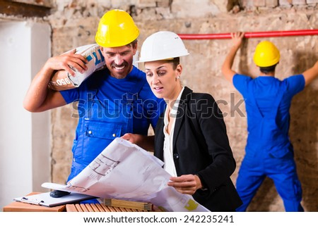 Architect and construction worker having sack of cement on shoulder on site with plan