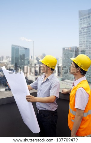 Architect And Construction Worker Talking On Rooftop - stock photo