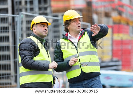 Architect and construction worker with yellow safety jacket and hardhat talking at construction site - stock photo