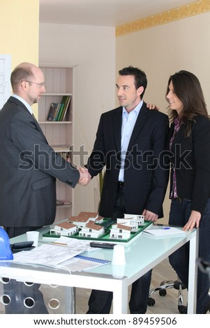Architect and couple stood by model housing - stock photo
