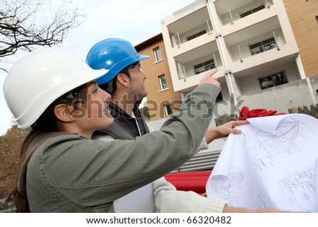 Architect and engineer looking at plan on construction site - stock photo