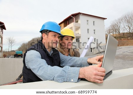Architect and engineer looking at plan on construction site