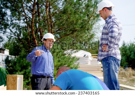 Architect and engineer working as a team standing on a building site having a discussion as a workman works in the foreground - stock photo