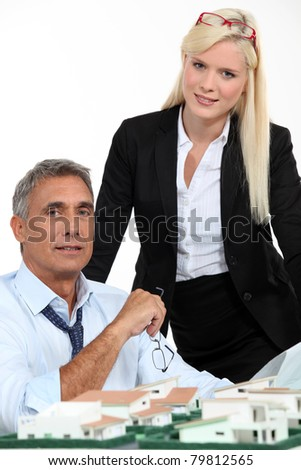 Architect and his assistant with plans and a 3D model - stock photo