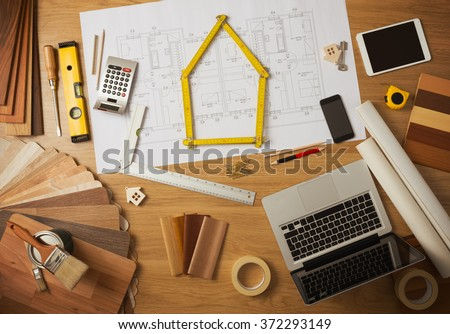Architect and home interior decorator desktop with tools, laptop, wood swatches and home project draft top view, a meter is composing a house at center - stock photo