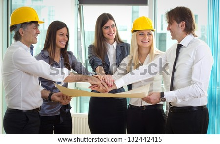 Architect and investors putting their hands together in a symbol of unity - stock photo