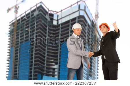 Architect and structural engineer shaking hands on a building site below a tall modern under construction as they congratulate each other or seal an agreement and partnership - stock photo