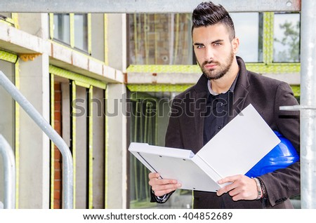 Architect at the construction site with protective cap keeps the document and plan or sketch, man holding document and reading from a folder on a construction scaffold