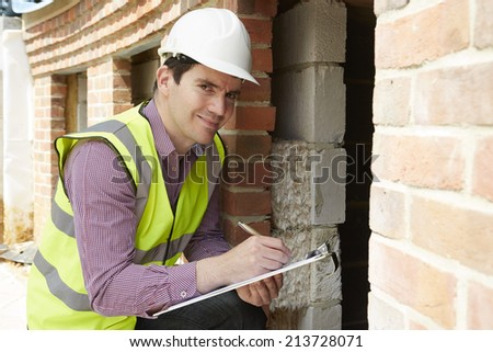 Architect Checking Insulation During House Construction - stock photo
