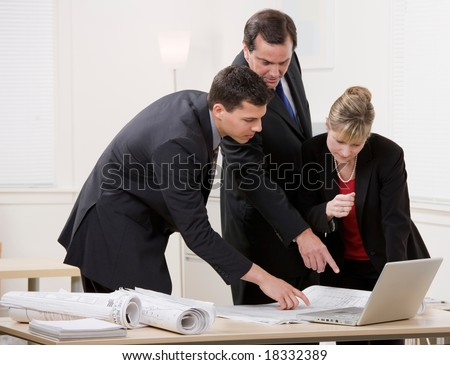 Architect co-workers collaborating on blueprints - stock photo