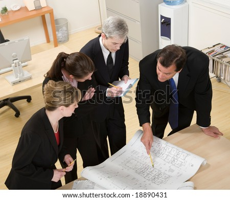 Architect co-workers reviewing blueprints - stock photo
