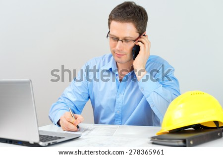 Architect discussing house plan with client by mobile phone. - stock photo