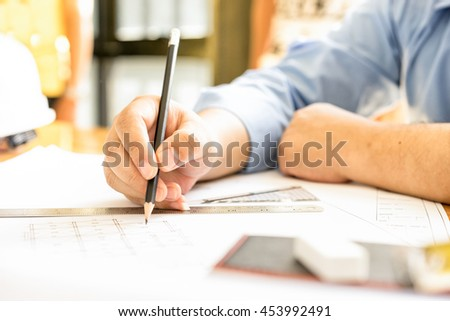 architect drawing architectural project on blueprint, engineering concept, architecture concept, soft focus, vintage tone