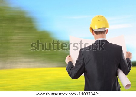 architect engineer expertise team plan talking hardhat in rapeseed field on sky background and forest trees Photo - stock photo