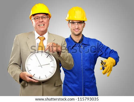 Architect Engineers Holding Clock And Plier On Gray Background - stock photo