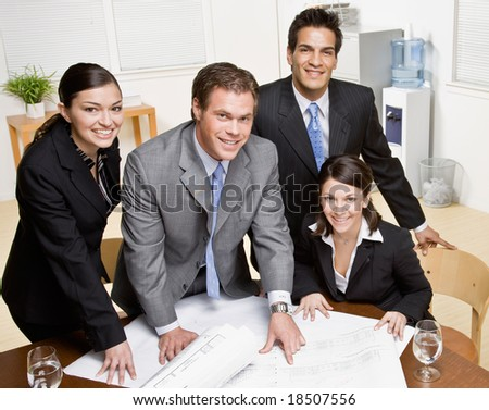 Architect explains issue on blueprint to co-workers in conference room - stock photo