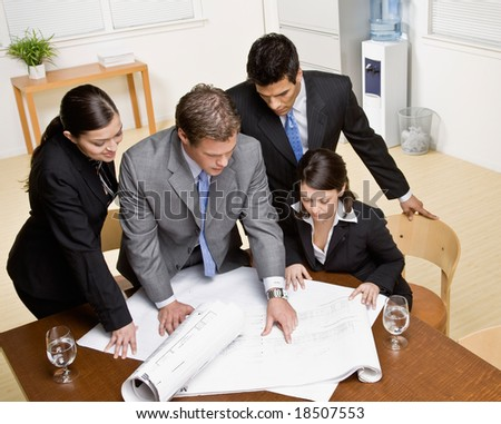 Architect explains problem on blueprint to co-workers in conference room - stock photo