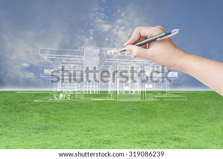 architect hand drawing a house on the grass field and sky background - stock photo