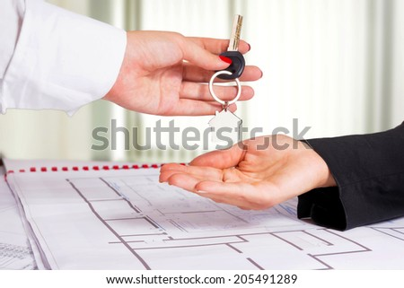 Architect hand presenting house key to a client. - stock photo