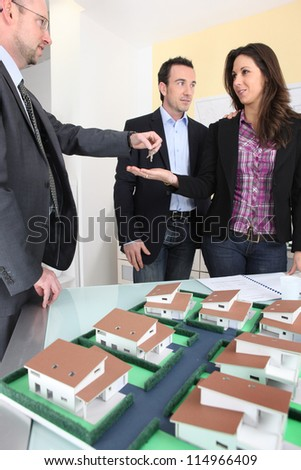 Architect handing over the keys to a new property owner - stock photo
