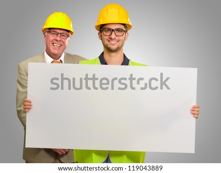 Architect Holding Placard On Gray Background - stock photo