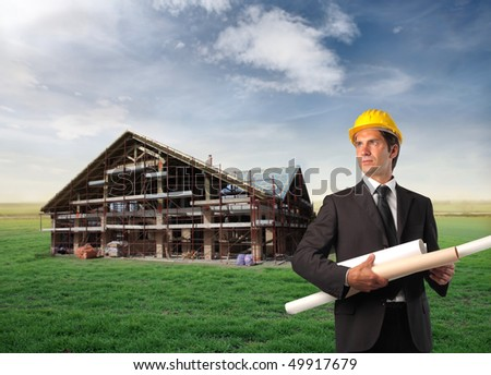Architect holding some project with a house in construction on a green meadow on the background - stock photo