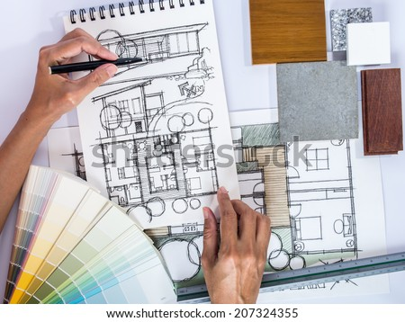 Architect /interior's hands drawing home illustration with material sample, renovation  concept - stock photo