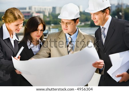Architect is holding his project of building and showing it to customers - stock photo