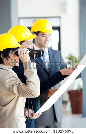 architect looking at construction site with binoculars - stock photo