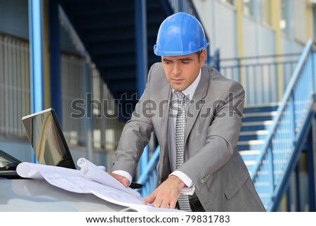 Architect looking at plans over a car - stock photo