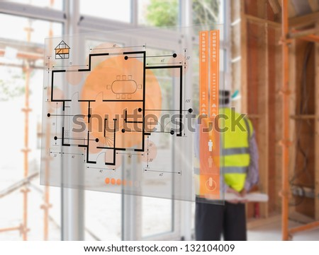 Architect looking out window with hologram interface depicting plan in foreground - stock photo