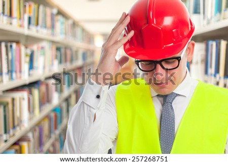 Architect man wearing a red helmet. He is looking tired. Over library background - stock photo