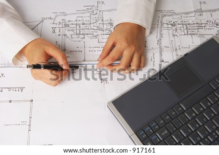 architect measuring plans with scale and a laptop by the side - stock photo